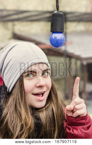 Beautiful white girl in warm winter clothes with excited face pointing at a blue light bulb with her finger. Aha thought idea concept human face expressions Earth Hour concept turn off the light