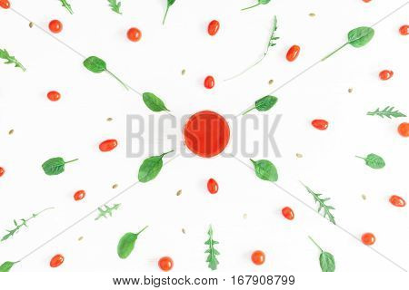 Fresh tomato juice cherry tomatoes arugula spinach leaves on white background. Flat lay top view