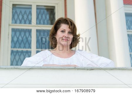 The woman is leaning on the parapet outside his home
