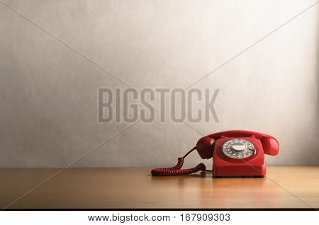 Retro Red Telephone On Light Wood Veneer Desk