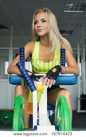 Active sexy blonde woman in sportswear sitting on sport equipment. Gym. Sports nutrition. Amino acids. Heavy weight