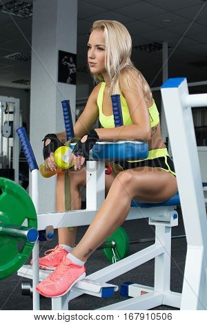 Active sexy blonde woman in sportswear sitting on sport equipment. Gym. Sports nutrition. Amino acids. Heavy weight. Shiny skin