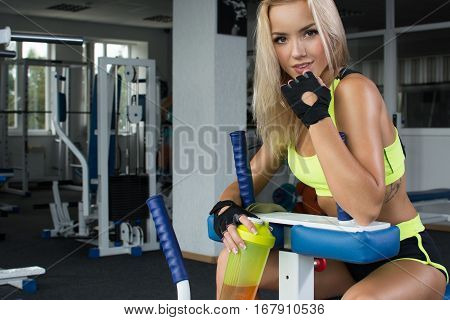 Active sexy blonde woman in sportswear sitting on sport equipment. Gym. Sports nutrition. Amino acids. Shiny skin
