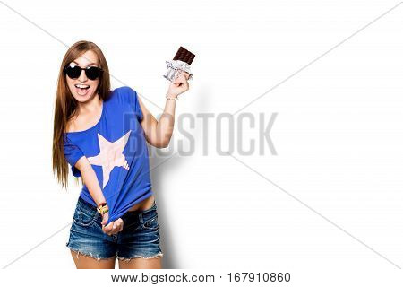 Beauty model woman eating dark chocolate. Beautiful Surprised young woman takes chocolate sweets, smiling and having fun. Funny girl, professional make up and bow hairstyle. White background.