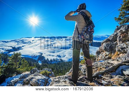 Female traveler is standing with on the edge of abyss above vast forest territory and winter mountains
