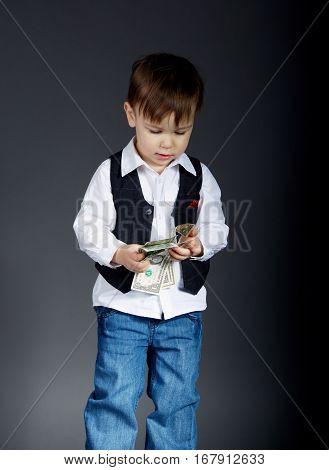 portrait of little boy counting money on dark background