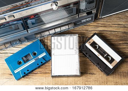 cassette tapes and cassette player on wooden table
