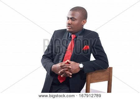 Portrait of handsome african business man wearing elegant black suite and red tie leaning on chair. Handsome male holding hands together and looking away. Studio isolate shot on white background.