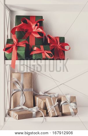 Colorful gift boxes wrapped in paper on white shelves in modern interior. Any holiday background with copy space. Christmas, birthday or valentine concept. High key