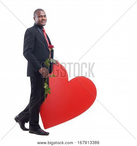 Full lenght portrait of african business man wearing black suite smiling at camera and holding red rose in hand. Male leaning of big red heart. Flower for girlfriend to Valentine Day. Isolate.