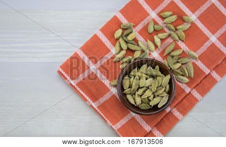 Bowl of Whole Bean Cardamom on orange plaid napkin