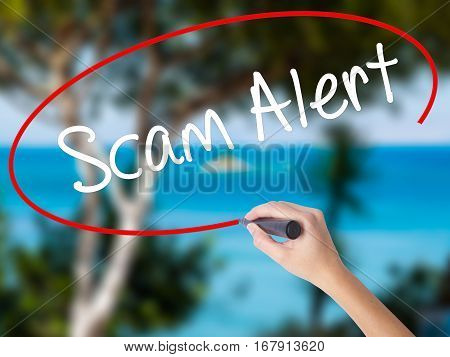 Woman Hand Writing Scam Alert  With Black Marker On Visual Screen