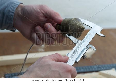 Carpenter workplace Check measurement of blank. Metal plummet in the form of a cone hanged on a rope.