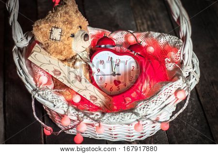 Decorations Valentine's Day. Teddy Bear an alarm clock and a festive envelope in the basket