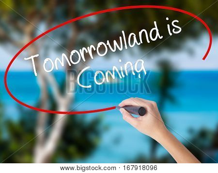 Woman Hand Writing Tomorrowland Is Coming With Black Marker On Visual Screen