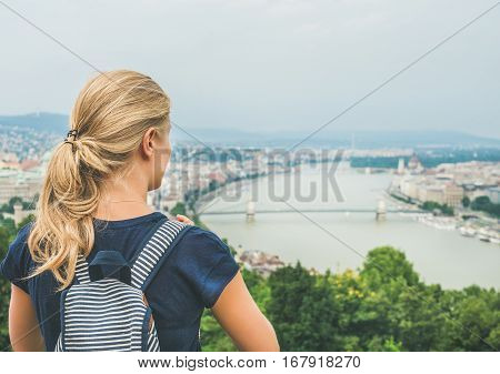 Young blond woman traveler with backpack looking at Danube and Budapest river from hill, rear view, Hungary