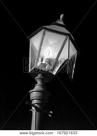 Broken hooligans street lamp in black and white. Streetlight as a symbol of vandalism. Vertical location.