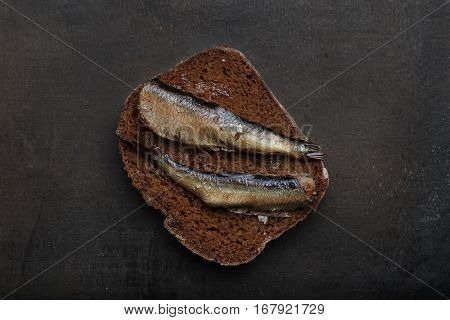 Snacks with sardines on black rye sliced bread. Riga traditional delicious dish. Smoked sprats on dark background. Top view.