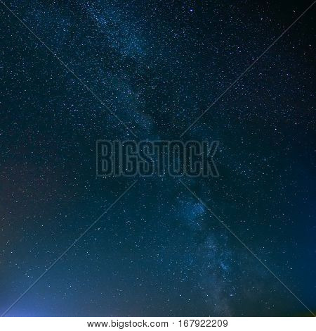 Blue Night Starry Sky Above Field And Yellow City Lights On Background. Night View Of Natural Glowing Stars Of Milky Way