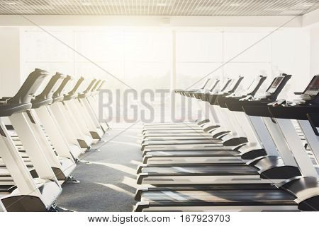Modern gym interior with equipment. Fitness club with row of treadmills for fitness cardio training in evening backlight. Healthy lifestyle concept