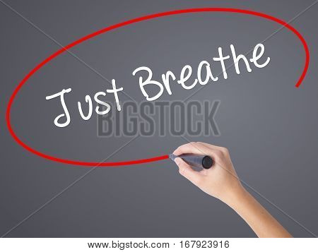 Woman Hand Writing Just Breathe With Black Marker On Visual Screen