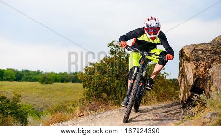 Professional Cyclist Riding the Bike at the Rocky Trail. Extreme Sport Concept. Free Space for Text.