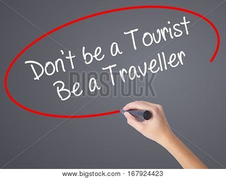 Woman Hand Writing Don't Be A Tourist Be A Traveller  With Black Marker On Visual Screen
