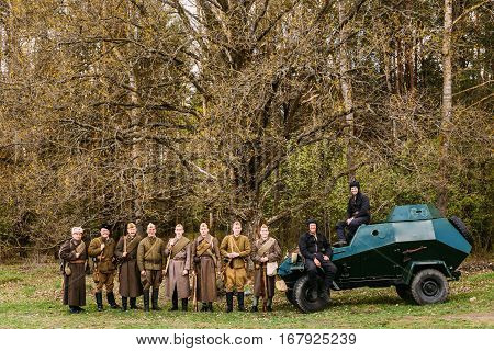 Pribor, Belarus - April 23, 2016: Unidentified Re-enactors Dressed As Russian Soviet Infantry Soldiers Of World War II Standing In Row At Armoured Soviet Scout Car BA-64 In Forest.