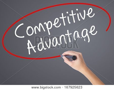 Woman Hand Writing Competitive Advantage With Black Marker On Visual Screen