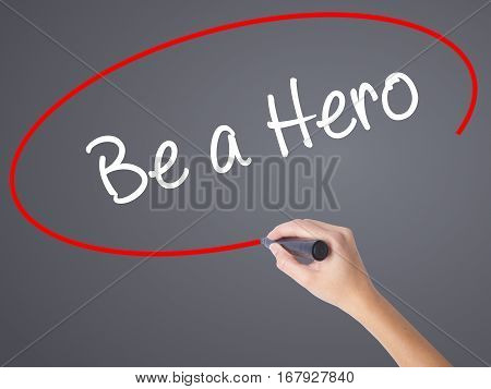 Woman Hand Writing Be A Hero  With Black Marker On Visual Screen
