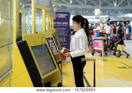 Young Asian businesswoman using self check-in kiosks in airport. Technology in airport.