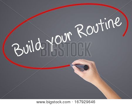 Woman Hand Writing Build Your Routine With Black Marker On Visual Screen