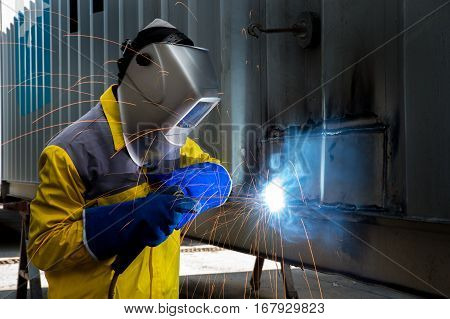 Industry worker with welding steel to repair container structures manufacture workshop in factory industry.