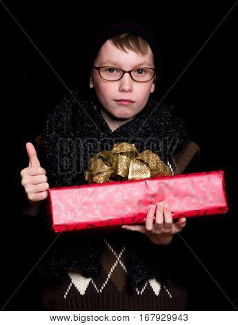 small boy or cute nerd kid in glasses hat and fashionable knitted scarf on black background holds red present box with golden bow and thumb up
