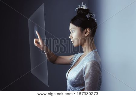 Young pretty asian female touching digital hologram screen. Future woman concept art. Fashion futuristic young attractive multi-racial Asian Caucasian model with futuristic make-up indoors. Copy space for your text.