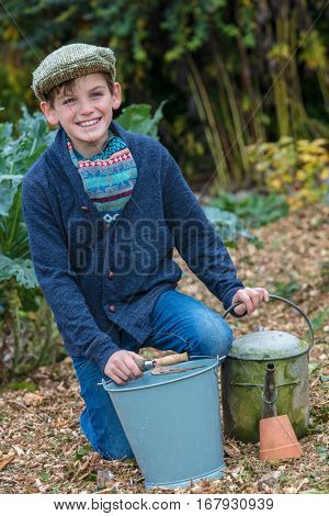Happy smiling male boy child wearing hat or flat cap, gardening with bucket, garden fork and watering can in a vegetable patch