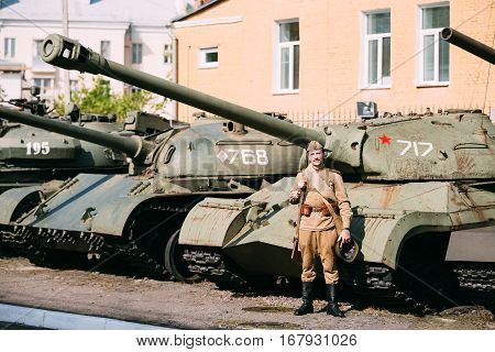 Gomel, Belarus - May 9, 2015: Unidentified re-enactor dressed as Soviet russian soldier posing near heavy tank IS-3