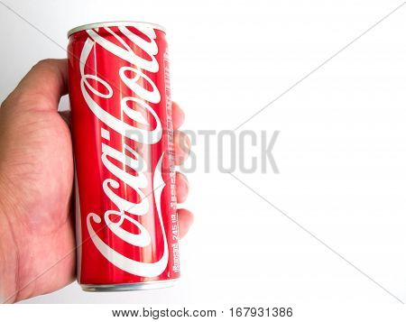 Bangkok Thailand January 27/2017 Hand hold classic Coca-Cola can on White Background. Coca Cola Coke is the most popular carbonated soft drink beverage