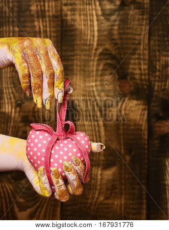female hand smeared in golden paint or glister holding handmade pink polka dots valentine heart on brown vintage studio background selective focus