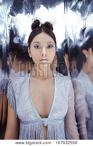 Portrait of futuristic scared young woman. Reflection of our mind and soul concept. Beautiful young multi-racial asian caucasian model cyber girl in silver urban clothes with conceptual hairstyle and make-up in metallik silver capsule.
