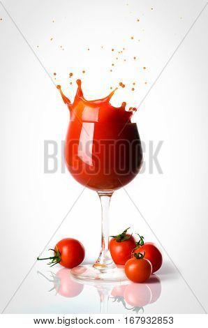 Splash o tomato juice in the glass and four small tomatoes seperated.