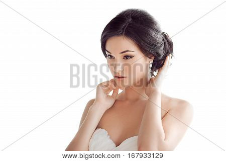 Beauty portrait of bride wearing wedding dress with feathers with luxury delight make-up and hairstyle, studio indoor photo. Young sensual multi-racial Asian Caucasian model sensual posing. Beautiful young woman like a bride isolated on white background l