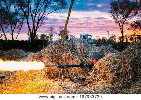 Mogilev, Belarus - May 8, 2015: Unidentified Re-enactor Dressed As Red Army Russian Soviet Infantry Soldier Machine-gunner Of World War II Fires His Machine Gun Out Of Hiding.