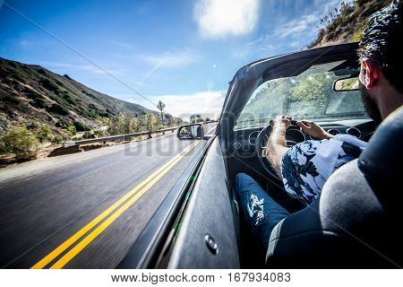 Man driving his sport car on the californian roads