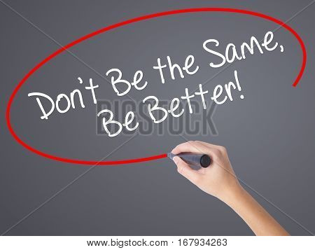 Woman Hand Writing Don't Be The Same, Be Better! With Black Marker On Visual Screen