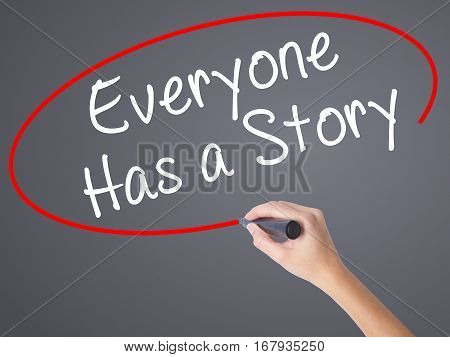 Woman Hand Writing Everyone Has A Story With Black Marker On Visual Screen