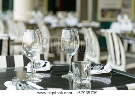 Empty wine glasses arranged on a table in an open air restaurant or bar.