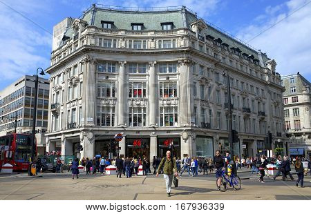 London, England - April 16, 2015: People crossing the busy junction of Regent Street and Oxford Street in front of the H&M store in London, England