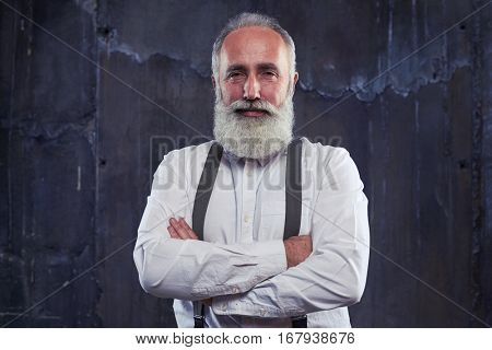 Close-up of handsome man. Holding arms folded isolated over black background. Man in formal clothes with suspenders. Shrewd look of mature man