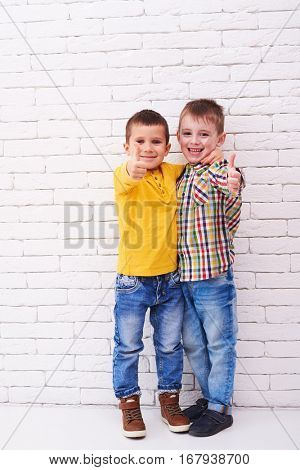 Mid shot of two exhilarating boys. Hugging each other and holding thumbs up. Toothy smile of two positive friends. Isolated over white background